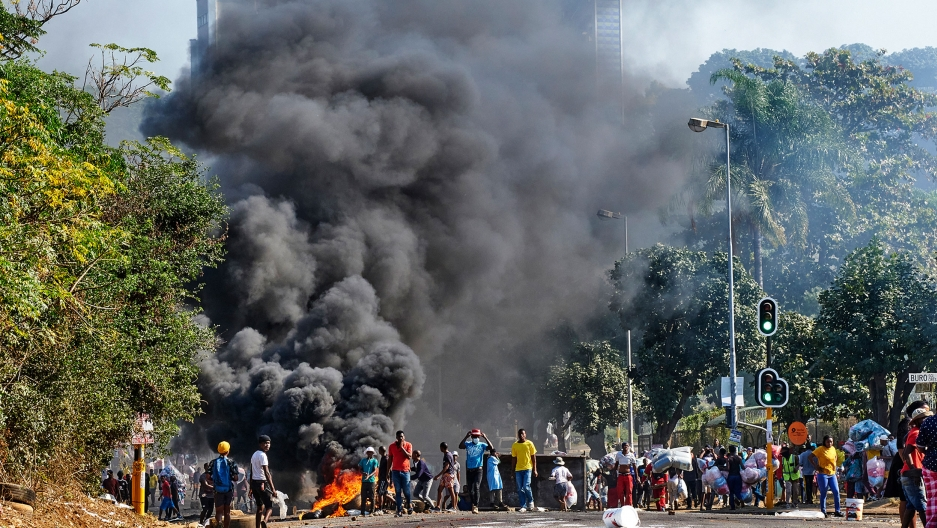 Looters outside a shopping centre alongside a burning barricade in Durban, South Africa