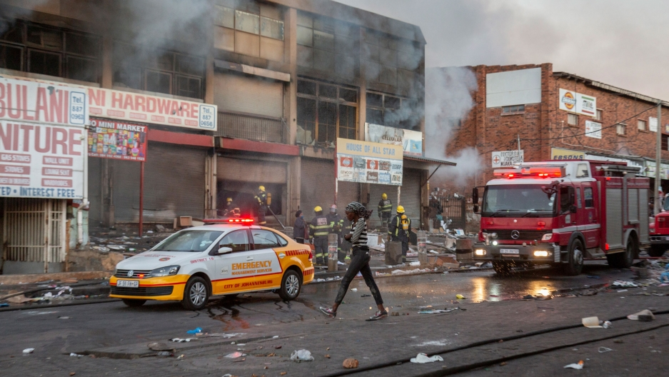 A woman is shown walking past a row of smoking buildings from a fire and fire trucks.
