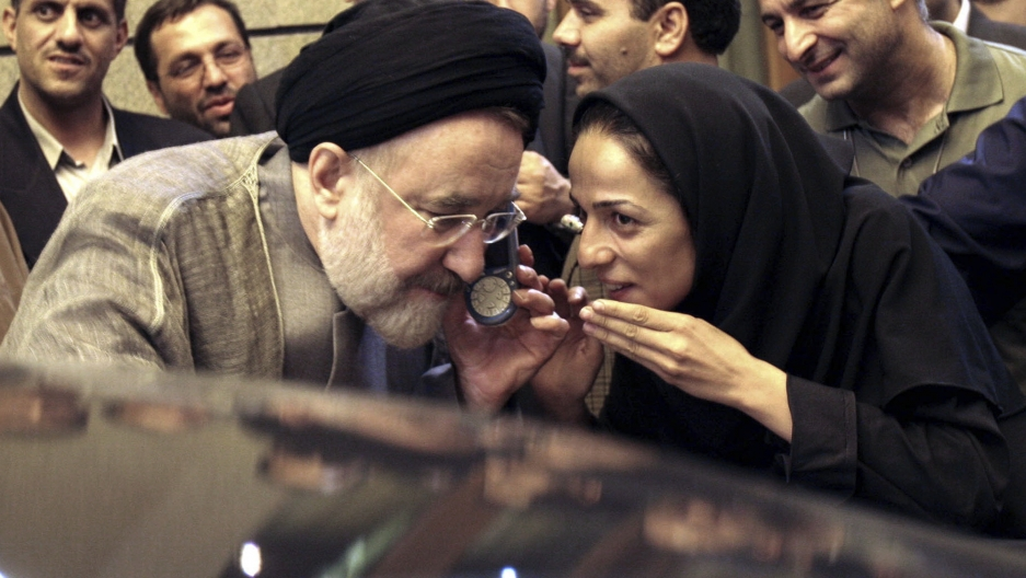 Outgoing reformist Iranian President Mohammad Khatami talks on the phone with the mother of female journalist Masih Alinejad, right, after meeting with journalists in Tehran, Iran, July 13, 2005.
