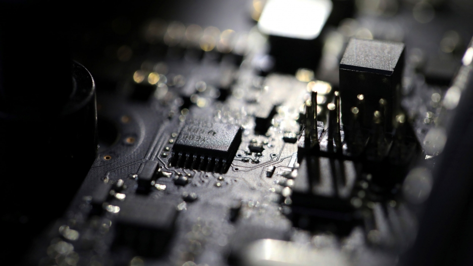 A close up photograph of a computer motherboard with circuits and microchips in high contrast light.