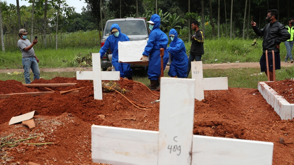 Several workers are shown wearing blue protective suits and carrying a white coffin while walking in at a grave site with several white crosses.