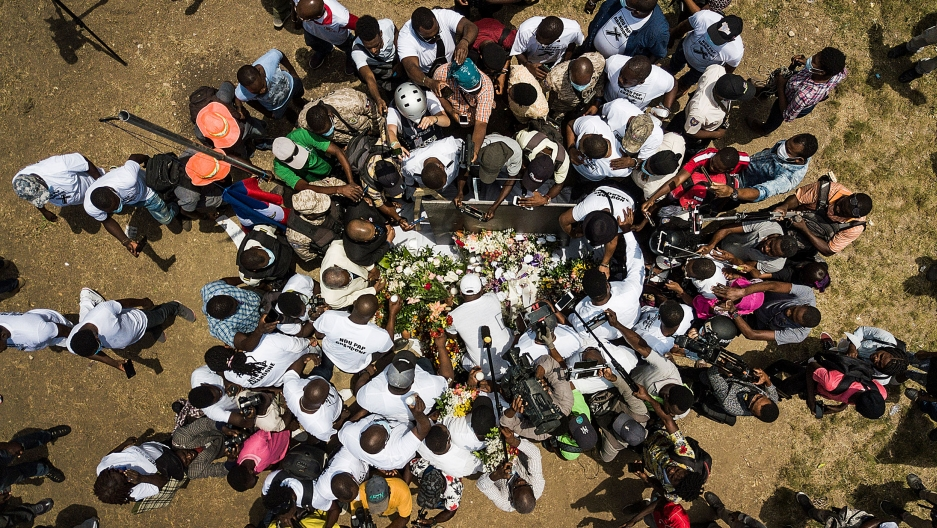 A large group of people are shown from above circling above a memorial of flowers.