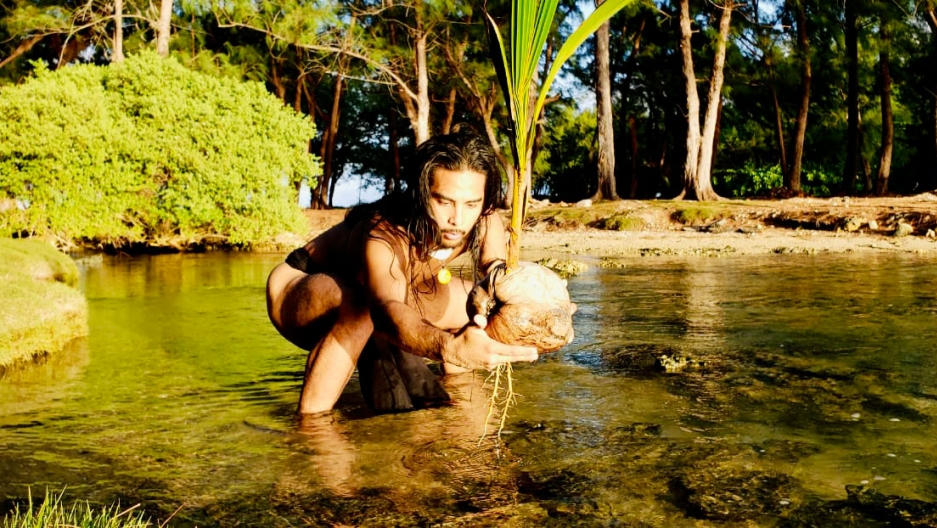 Dakota Camacho, dancer and musician, seen in a body of a water unclothed with long hair.