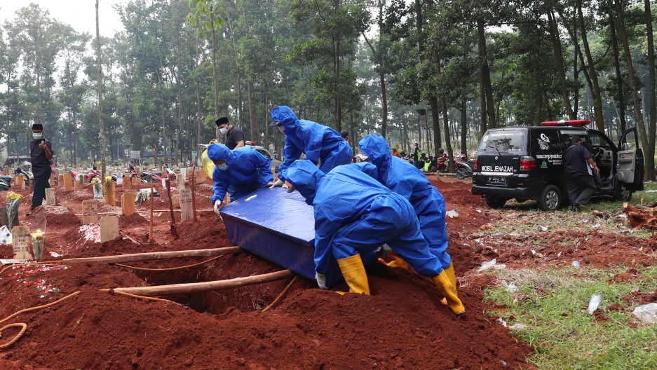 Workers in protective suits carry a coffin containing the body of a COVID-19 victim to a grave for a burial at Cipenjo cemetery in Bogor, West Java, Indonesia, Wednesday, July 14, 2021.
