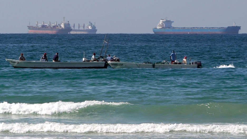 Two small fishing boats are shown in the near ground with large oil tankers off in the distance.
