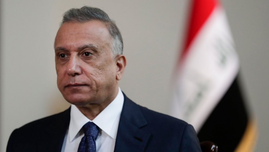 Iraqi Prime Minister Mustafa al-Kadhimi is shown wearing a dark suit and tie with the Iraqi national flag in soft focus in the background.