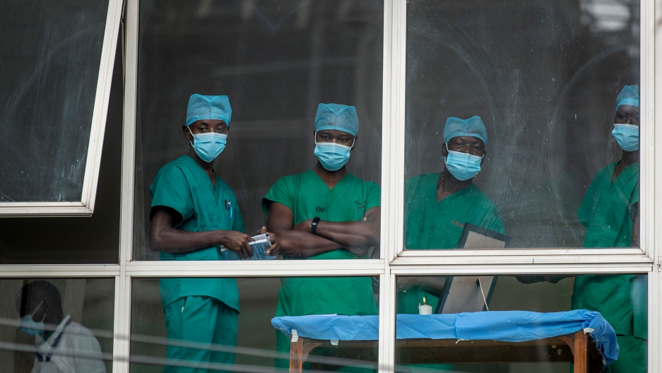 Four people are shown looking through a white-framed windows and wearing green medical scrubs.