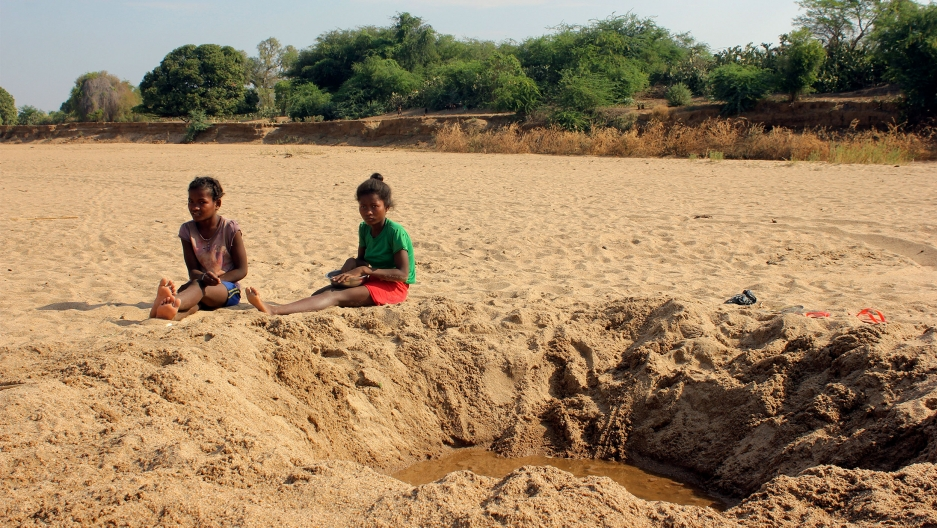 Children sit by a dug out water hole in a dry river bed in the remote village of Fenoarivo, Madagascar