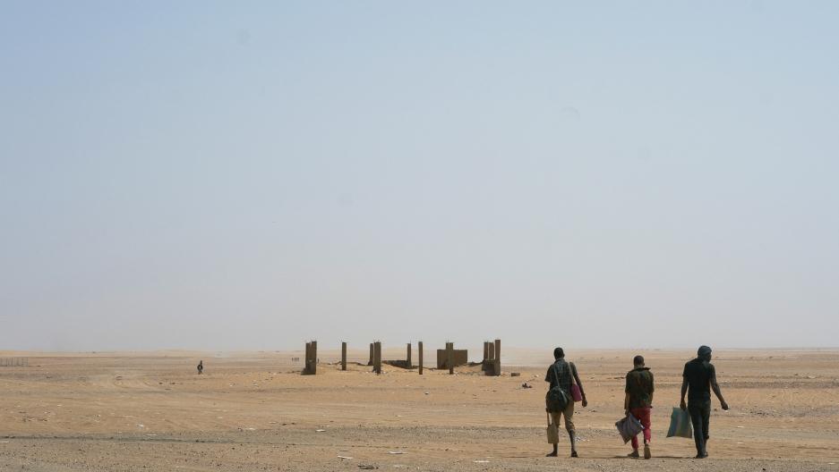 Three men head north towardAlgeria after crossing the Assamaka border post in northern Niger, June 3, 2018.