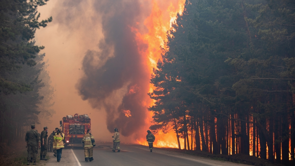 Firefighters work at the scene of a forest fire near Andreyevsky village outside Tyumen, western Siberia, Russia,June 16, 2021.