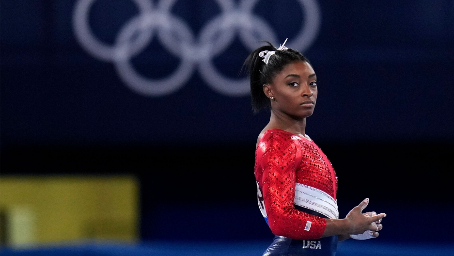 Simone Biles is shown in a profile photograph looking to her right, wearing a red, white and blue uniform with the Olympic rings in the distance.