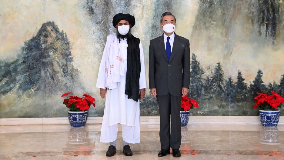 Taliban co-founder Mullah Abdul Ghani Baradar is shown wearing traditional white robes while standing next to and Chinese Foreign Minister Wang Yi wearing a suit.