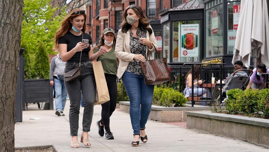 Pedestrians walk along Boston's fashionable Newbury Street, Sunday, May 2, 2021.