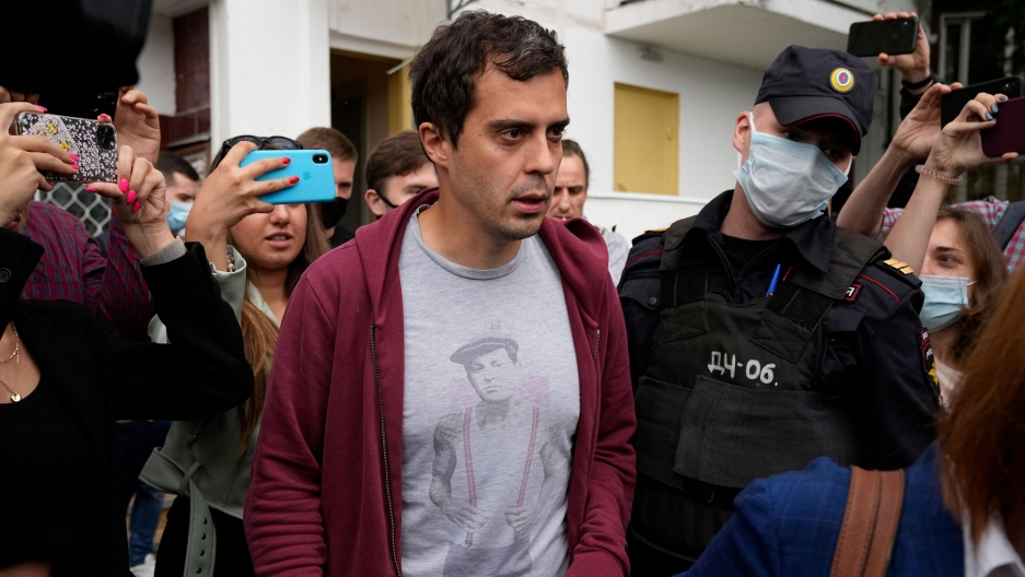 A man wearing a red cardigan with dark hair walks near a police officer.