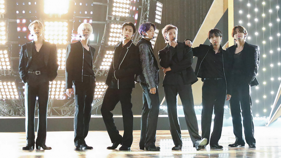 Members of BTS standing on a stage with dramatic lighting