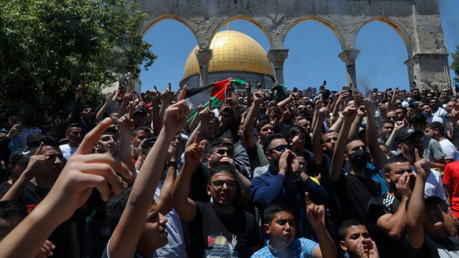 Palestinians chant slogans during a protest in front of the Dome of the Rock Mosque at the Al Aqsa Mosque compound in Jerusalem's Old City, Friday, June 18, 2021.