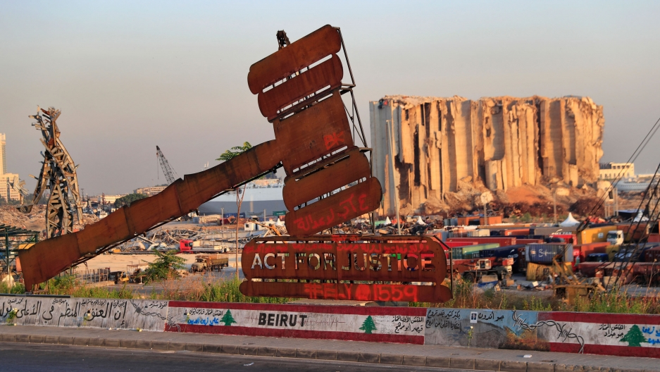 """A large gavel made of metal is shown in the near ground hammering a sign that reads """"Act for Justice"""" with a bombed out grain silo in the distance."""