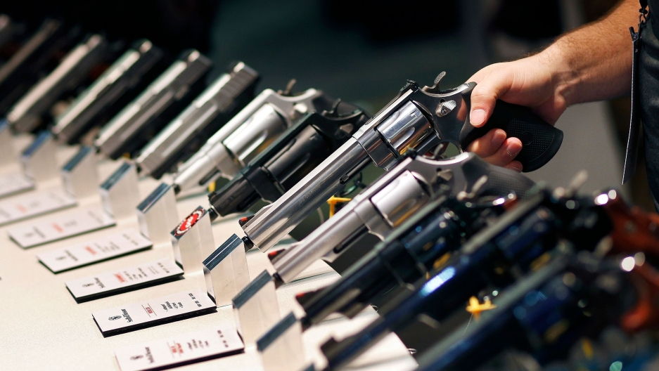 A row of handguns are shown with the handle facing outward and a hand holding on to one of the weapons.