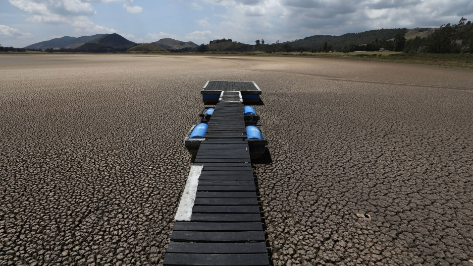 A long wooden dock is shown with blue barrels on both sides on the dry bed where a lake used to be.