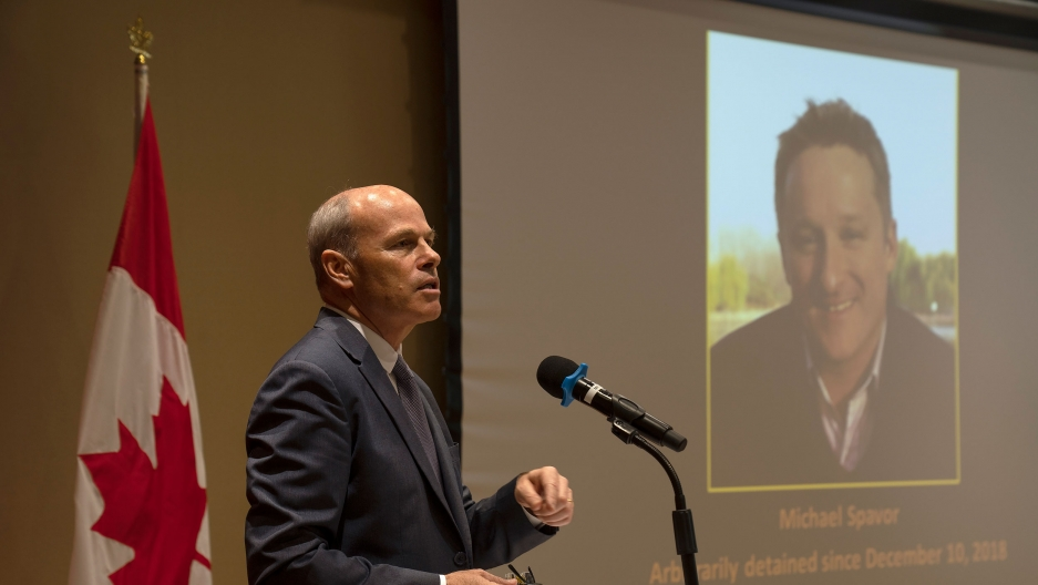 Jim Nickel is shown wearing a suit and tie while speaking into a microphone with an image of Michael Spavor projected on a screen in the background.