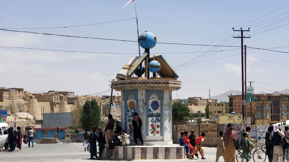 Several people are shown sitting and standing around the center, circular post in the open air city square.