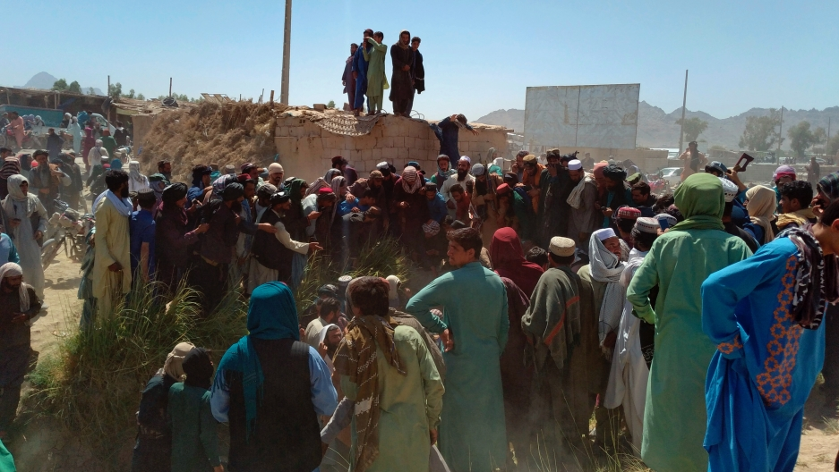 Taliban fighters and Afghans gather around the body of a member of the security forces who was killed