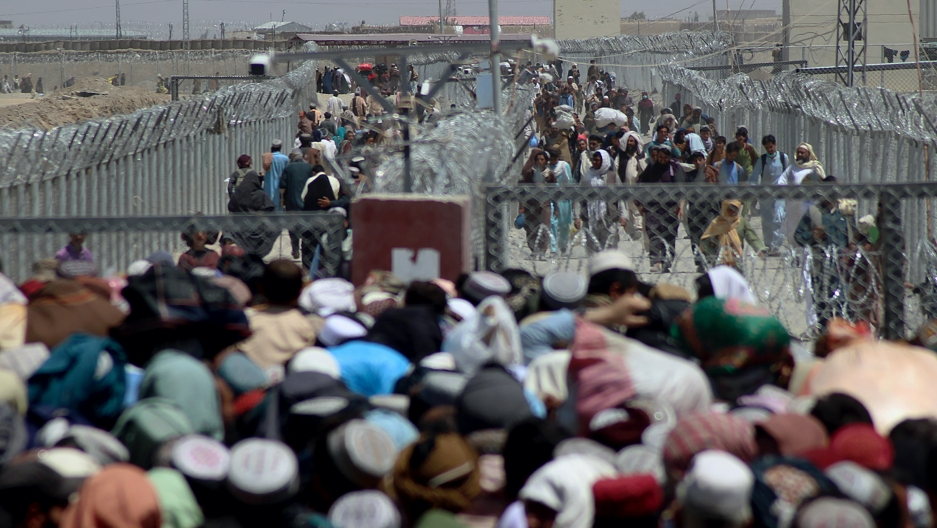 Stranded people crossing the border between Pakistan Afghanistan, in Chaman, Pakistan, Aug. 13, 2021. Pakistan opened its Chaman border crossing for people who had been stranded in recent weeks. Juma Khan, the Pakistan border town's deputy commissioner, s
