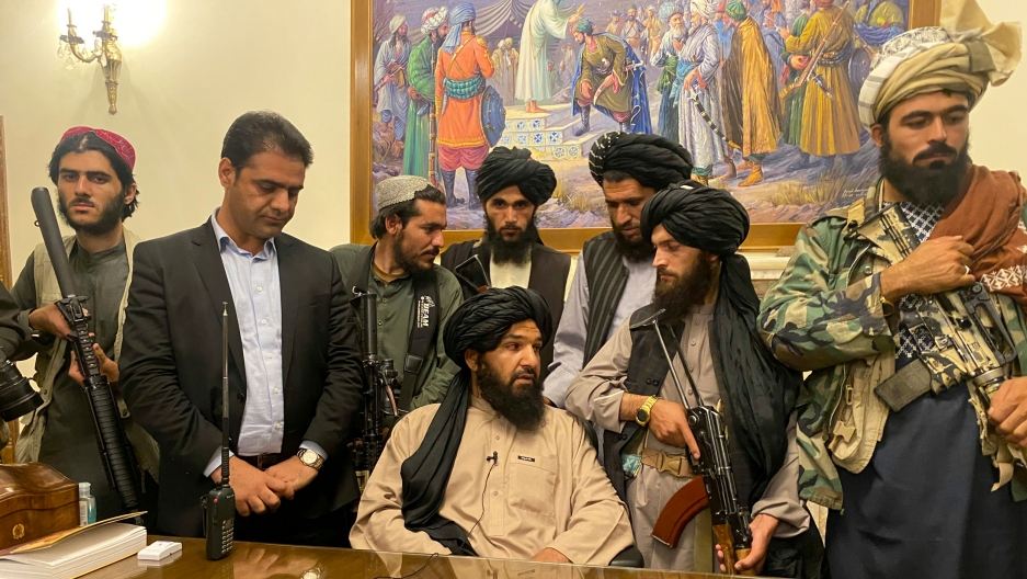Several Taliban fighters are shown standing around a large wooden table with one man sitting down.