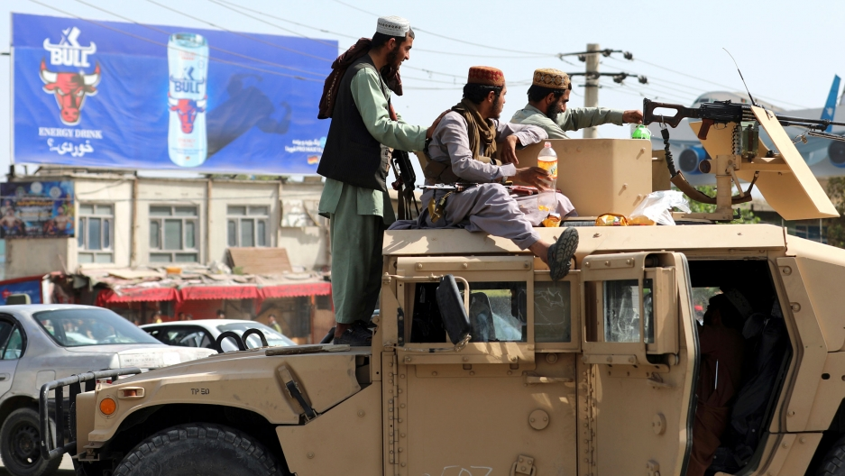 Several members of the Taliban are shown atop a tan-color Humvee with a large weapon on top.
