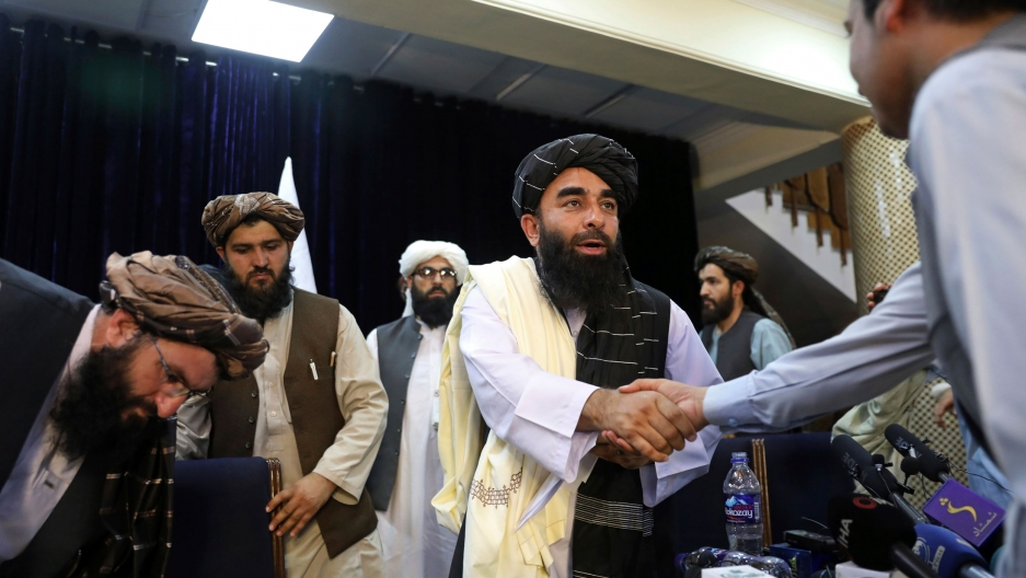 Taliban spokesman Zabihullah Mujahid shakes hand with a journalist after his first news conference, in Kabul, Afghanistan, Tuesday, Aug. 17, 2021.