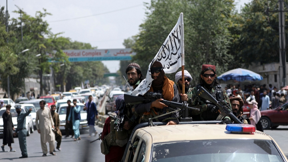 A group of heavily armed bearded men are shown riding in the back of a police pickup truck.