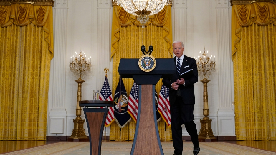 US President Joe Biden is shown walking toward a podium with the seal of the US presidency and holding a folder.