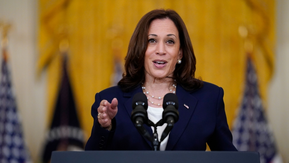 Vice President Kamala Harris is shown standing at a podium with two microphones and her right hand pointing forward.