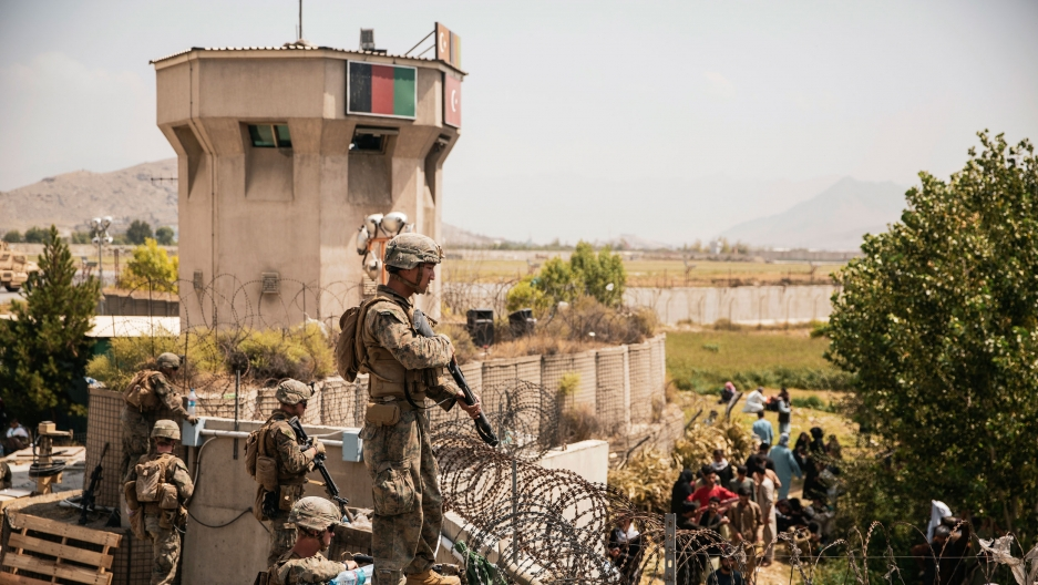 In this image provided by the US Marine Corps, Marines assist with security at an evacuation control checkpoint during an evacuation at Hamid Karzai International Airport in Kabul, Afghanistan, Friday, Aug. 20, 2021.