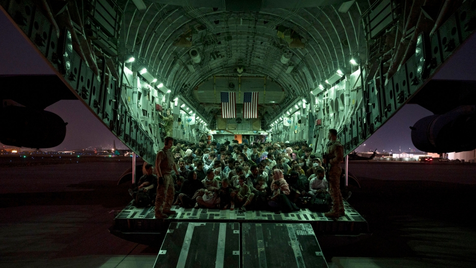 A large group of evacuees are shown in the back of a large Air Force aircraft with green-colored lights lining the inside.