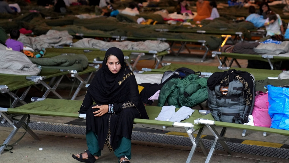 A young woman is shown sitting on a green cot, among dozens over other cots, each with personal belongings on top.
