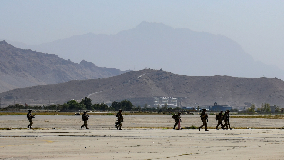 Several military officers are shown in a line, and heavily armed, walking on an open tarmac area with mountains in the distance.