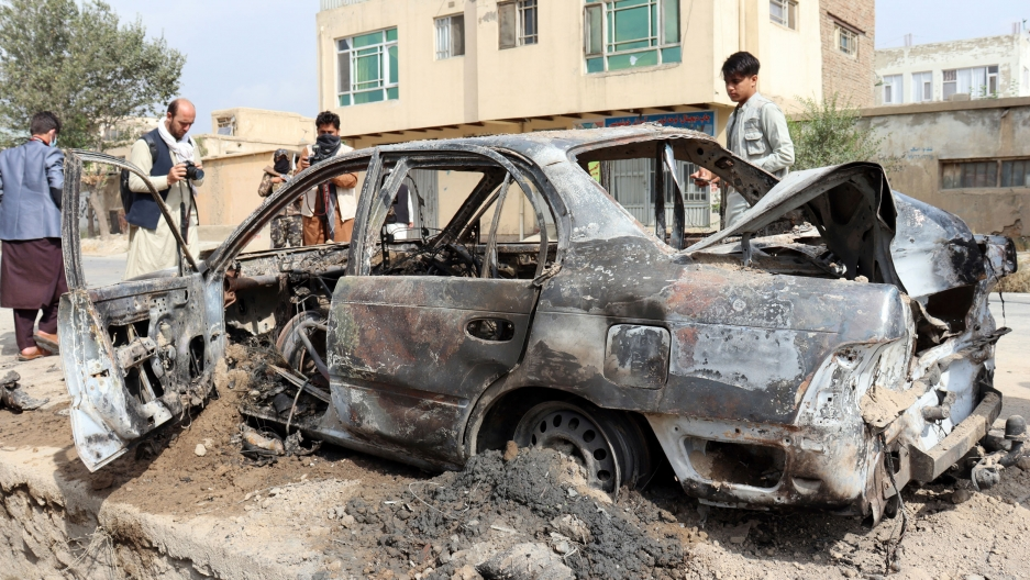Several people are shown standing around a bombed out car, chared from the explosion.