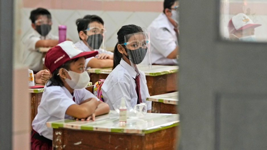 Several young school children are shown sitting at desks with one girl looking back at the camera while wearing a clear face shield and mask.