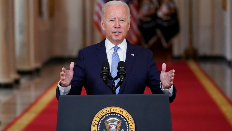 US President Joe Biden is shown standing at a podium and speaking into a microphone with his hands raised slightly.