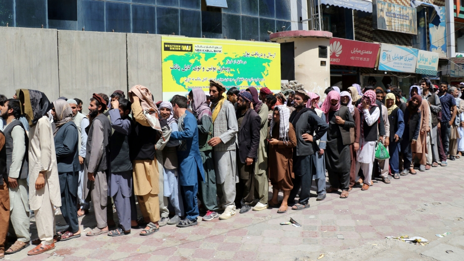 Afghans wait in front of Kabul Bank, in Kabul, Afghanistan, Wednesday, Aug. 25, 2021.