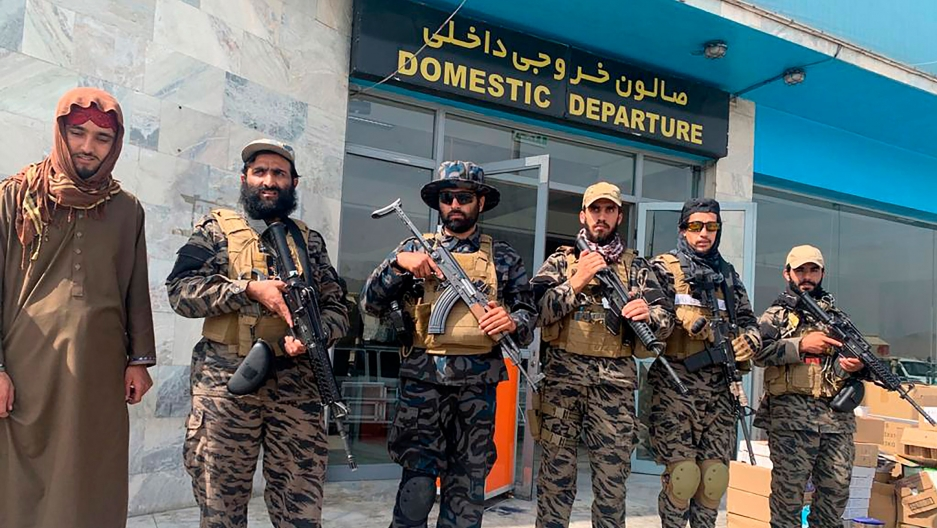 A group of six men are shown holding guns and wearing military fatigues with the domestic departure entrance to the Kabul airport.
