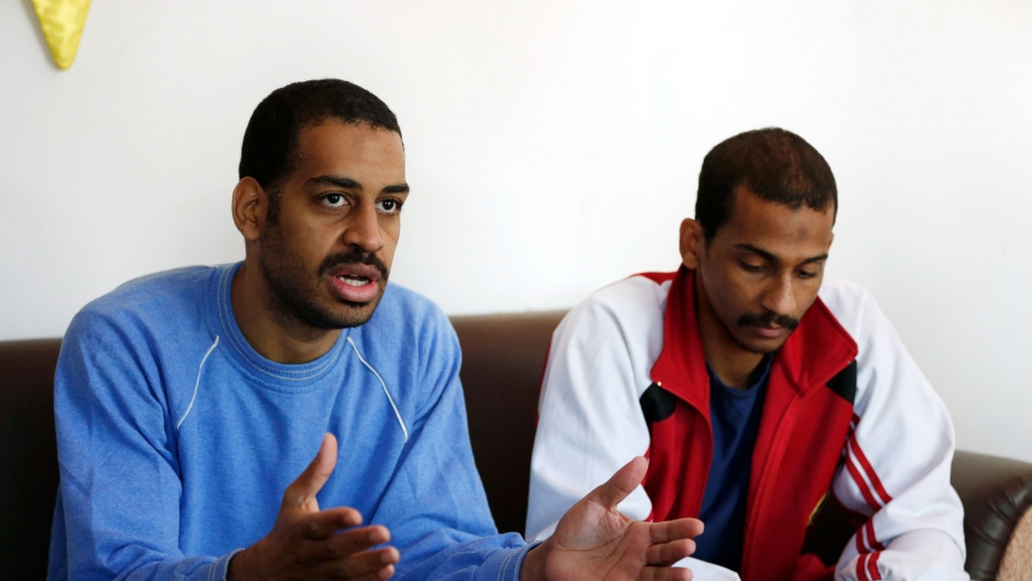 Two men are shown sitting on a sofa with Alexanda Amon Kotey on the left, wearing a blue sweatshirt.