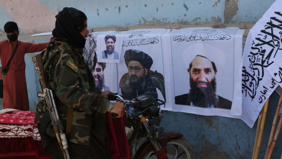 Taliban fighter looks at Taliban flags and posters of leaders in Kabul, Afghanistan, Wednesday, Aug. 25, 2021.