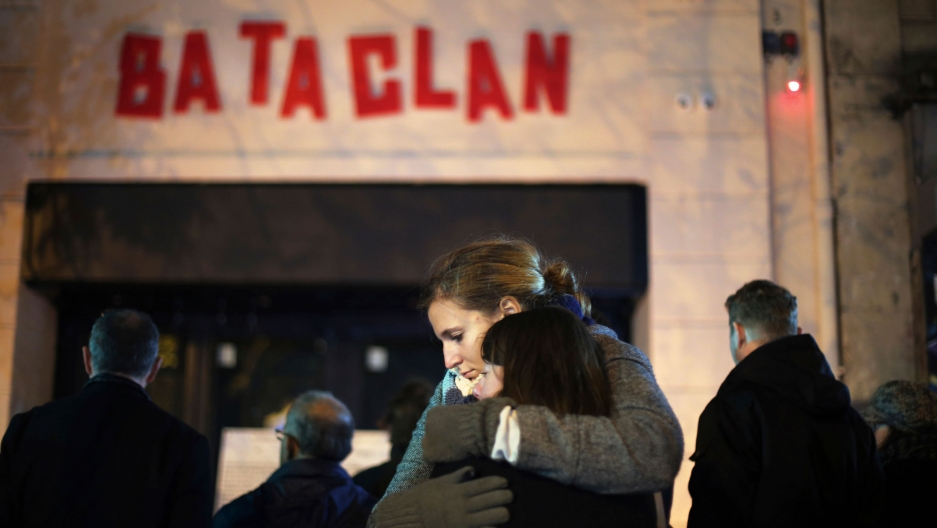 Two women are shown hugging each other with the entrance and red-lettered sign of the Bataclan concert hall in the background.