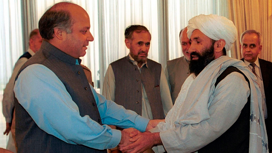 Mullah Hasan Akhund is shown wearing a white head wrap and standing across from Nawaz Sharif who is wearing a gray vest and blue shirt.