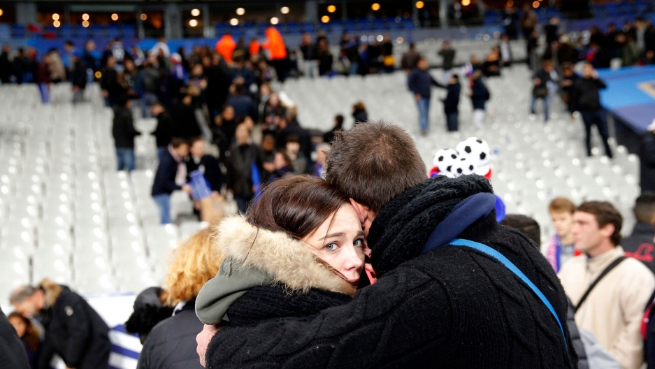 A man is shown hugging a woman who is looking into the camera with empty stadium seats in the distance.