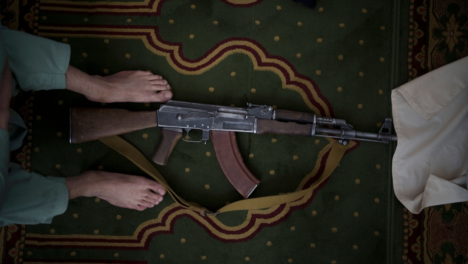 A Taliban fighter lays his AK-47 rifle down during Friday prayers at a mosque in Kabul, Afghanistan, Friday, Sept. 10, 2021.