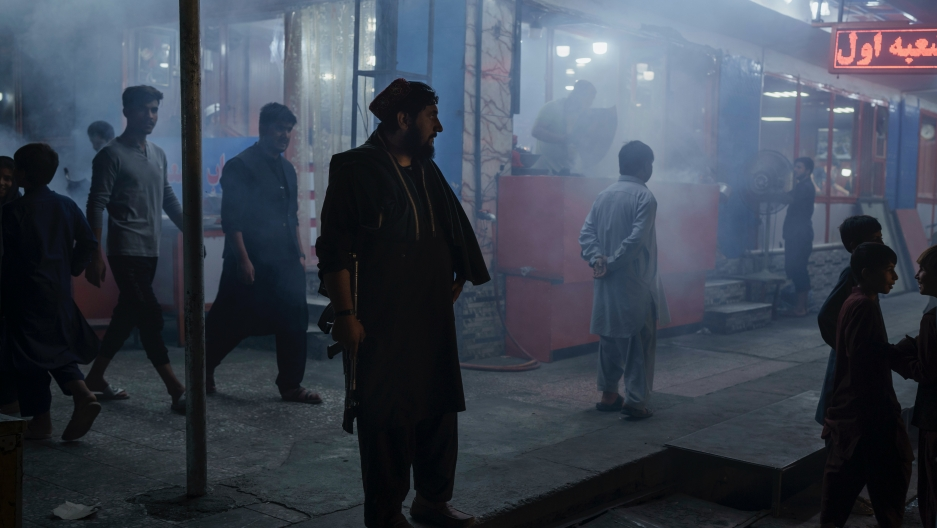 A Taliban fighter stands in the corner of a busy street at night in Kabul, Afghanistan, Sept. 17, 2021.