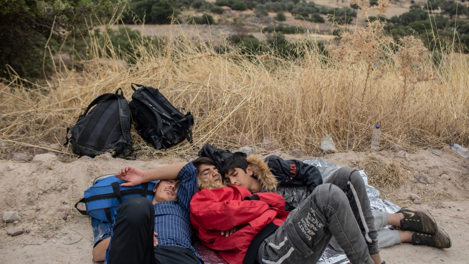In this Monday, Oct. 7, 2019 photo, exhausted Afghan youths sleep on the ground near the town of Madamados after their arrival with other migrants and refugees on a rubber boat from Turkey, at Lesbos Island, Greece.